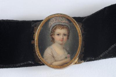 English School late 18th /early 19th century - Miniature portrait of a girl said to be 'Beatrice bought at Strawberry Hill' with rosy cheeks and brown eyes wearing a bonnet and white silk dress and holding a pink rose, oval, 3.3cm, in a yellow metal frame and choker clasp.