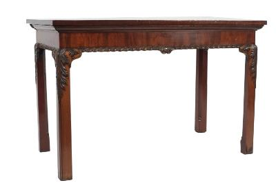 Sale FS21; Lot: 0901: A pair of George III carved mahogany pier tables, with later rectangular tops and moulded friezes, having gadrooned aprons, centred by foliate scroll designs, raised on moulded square chamfered legs, headed with acanthus leaves - The tops were probably originally with marble, now measuring 131.5cm (4ft 3 3/4in) and 133cm (4ft 4 1/4in) x 71cm (2ft 4in).