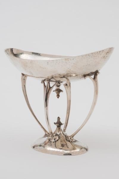 An Arts & Crafts silver sweetmeat dish, maker Mappin & Webb, London, 1906 the oval hammered bowl supported on four curved tendril style supports, raised on an oval domed foot, 205cm wide, 1486ozs.