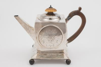 A George III silver teapot, maker IR possibly John Robins, London, 1799 crested, of square form, the side with engraved floral circular panels, with similar decoration to the hinged lid, raised on squat bracket feet, 16cm high, on a later Victorian square stand, raised on ball feet, maker Edward, John, William and James Barnard, London, 1870, total weight of silver 2046ozs.