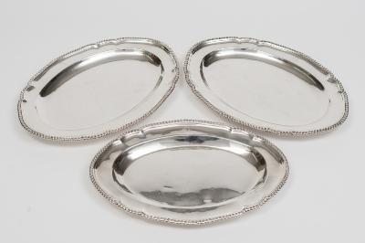 A pair of George III silver oval platters and one matching, maker John Parker & Edward Wakelin, London 1772 crested, with gadrooned borders, 36cm wide together with a smaller matching platter, 33cm wide, total weight of silver 6931ozs.