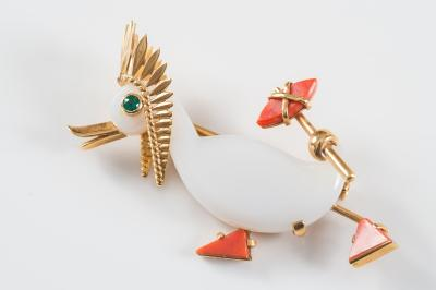 Sale FS22; Lot: 0233: Cartier. An 18ct gold, agate, emerald and coral mounted 'novelty duck' brooch, the duck wearing Indian headdress and carrying an axe with agate body, circular emerald eye and coral feet, 51mm long overall, inscribed 'Cartier France 18kts', import hallmarks for London 1952, inscribed number worn, in fitted gilt tooled red leather case stamped 'Cartier'.