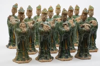 A set of twelve Chinese pottery male tomb attendants each modelled standing in flowing robes and wearing elegant head wear, their hands crossed supporting a zodiac animal, on hexagonal base, 33cm high, Ming Dynasty, minor loss to odd figure.