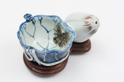 A Chinese underglaze blue and copper-red lotus water-dropper formed as a lotus leaf with attached seed-pod, the leaf with painted and applied veins and stems, a crab with sepia markings climbing down into the open leaf, the bud petals hightened with copper-red, Kangxi, 12cm wide and wood stand.