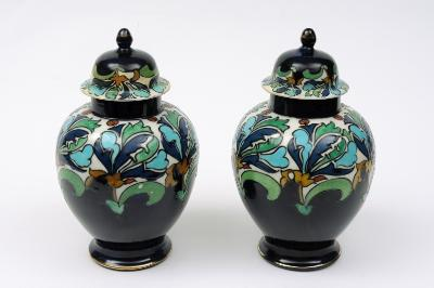 Charlotte Rhead for Wood & Sons a pair of jars and covers each of oviform with domed covers tubelined in the Persian pattern with a cream band of green, blue, turquoise, yellow and red spiky leaves and buds above a blue ground, 26cm high, printed mark and painted X.775, circa 1915, covers restored.