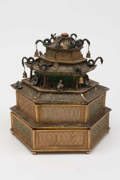A Chinese paper and card stacking table top box. in the form of a hexagonal pagoda, the roof with serpent shaped bell holders and pottery figures, with six lift-off sections containing fitted compartments, the base with lift-out circular chest containing fifty four miniature drawers, 27cm wide 29cm high.