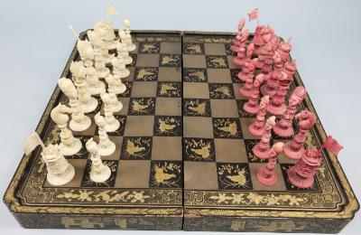 An early 19th century 'Macao Export' ivory chess set one side stained red, the other side left natural, Europeans versus Chinese, red King and Queen as European monarchs, bishops as clergy, white King and Queen as Emperor and Empress, white bishops as Mandarins, knights as horses heads, rooks as foliate towers, red rook bearing Union flag, the pawns as attendants, the King 11cm high, the rook 65cm high, contained in a black lacquer and gilt decorated folding chess board with backgammon to the interior.