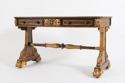 A Regency rosewood and carved giltwood library table, the rectangular top with rounded corners and a gilt reeded edge, containing two short drawers in the frieze with central raised gilt panel of scrolling acanthus, anthemions and central flowerhead, having paterae to the rounded corners, on solid standard dual trestle end supports with reeded scroll work, flowerhead roundels and foliage, terminating in foliate scroll feet and castors, the top 128cm (4ft 2 1/4in) x 67cm (2ft 2 1/2in).