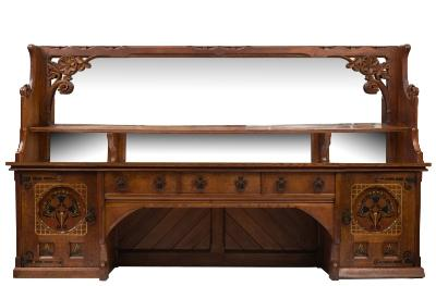 Designed by William White for Bishops Court, Exeter - An oak Gothic revival sideboard, the mirrored superstructure with a shelf and carved with scrolling foliage and a flowerhead, the base of breakfront outline fitted with three drawers, flanked by two panelled doors with polychrome decoration and iron strapwork hinges, 331.5cm (10ft 10 1/2in) long, 194cm (6ft 5 1/4in) high.