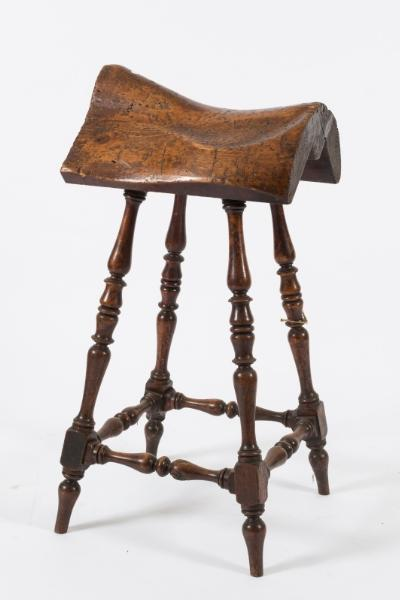 A rare Victorian pine and fruitwood saddle template stool, on turned and tapered splayed legs, united by stretchers.