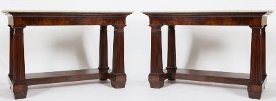 A pair of 19th Century French mahogany console tables, each surmounted by a rectangular panel of white marble, having curved friezes, on square section fluted legs, united by recessed breakfront undertiers, terminating in spade feet, the tops 158cm (5ft 2in) x 60cm (1ft 11 1/2in).