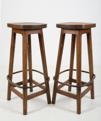 By Robert Thompson of Kilburn - A set of six 'Mouseman' oak bar stools, the oval shaped seats on octagonal splayed legs, with metal foot rests and united by plain stretchers, each stool carved with the mouse, 77.5cm (2ft 6 1/2in) high, the seats 38cm (1ft 3in) x 29cm (11 1/2in).