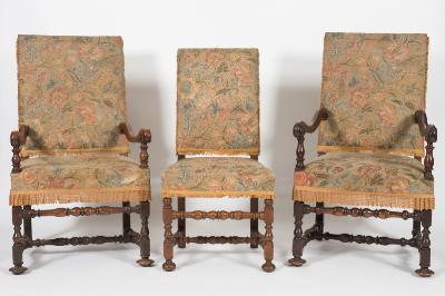 A matched set of eight 17th Century and later walnut dining chairs, with upholstered stuff over rectangular backs and seats in floral foliate tapestry, on baluster turned legs, united by similar stretchers - including a pair of elbow chairs.