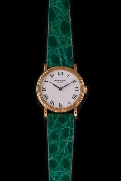 Sale FS24; Lot: 0116: Patek Philippe. A lady's 'Patek Philippe' wristwatch, the signed, circular white enamel dial with Roman numerals within a grained bezel surround on green coloured strap stamped 'Patek Philippe Geneve' contained in a signed, maroon leather case, together with certificate of origin confirming date of purchase as '1997'.
