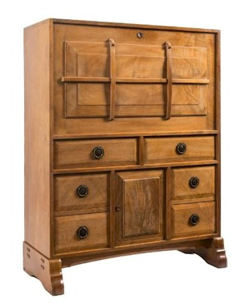Sale FS24; Lot: 0868: By Peter Waals (1870-1937) - Cotswold School - A walnut secretaire cabinet, the hinged fall with raised moulded and strapped panel enclosing a fitted and chequer inlaid interior with pigeon holes, seven small drawers and a central enclosed cupboard, having a leather inset writing surface containing an arrangement of six short fielded panel drawers and an enclosed cupboard below, on shaped trestle ends with arched chamfered stretcher, 101cm (3ft 3 3/4in) wide, 130cm (4ft 3in) high. *Note - A somewhat similar secretaire was sold in the contents of Topps, Stockton, Warminster, Woolley & Wallis October 1978.