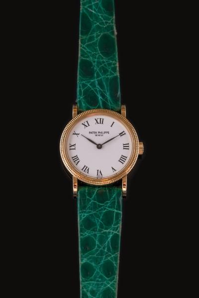 Patek Philippe. A lady's 'Patek Philippe' wristwatch, the signed, circular white enamel dial with Roman numerals within a grained bezel surround on green coloured strap stamped 'Patek Philippe Geneve' contained in a signed, maroon leather case, together with certificate of origin confirming date of purchase as '1997'.