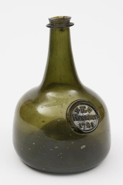 An early 18th century sealed mallet shaped wine bottle of medium green colour and of small size with raised tapering neck and string rim, with pronounced 'kick up', the shoulders with a seal for 'E. Herbert, 1721, 16cm high, minor chips to rim.