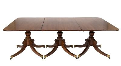 A Regency and later mahogany triple pillar dining table, the top with a reeded edge and rounded corners, on turned vase knopped columns and quadruped hipped and reeded splayed legs, terminating in brass cappings and castors, the top 138cm (4ft 6 1/4in) x 223.5cm (7ft 4in) and with two additional leaves extending to 323.5cm (10ft 7 1/2in).