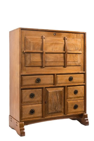 By Peter Waals (1870-1937) - Cotswold School - A walnut secretaire cabinet, the hinged fall with raised moulded and strapped panel enclosing a fitted and chequer inlaid interior with pigeon holes, seven small drawers and a central enclosed cupboard, having a leather inset writing surface containing an arrangement of six short fielded panel drawers and an enclosed cupboard below, on shaped trestle ends with arched chamfered stretcher, 101cm (3ft 3 3/4in) wide, 130cm (4ft 3in) high. *Note - A somewhat similar secretaire was sold in the contents of Topps, Stockton, Warminster, Woolley & Wallis October 1978.