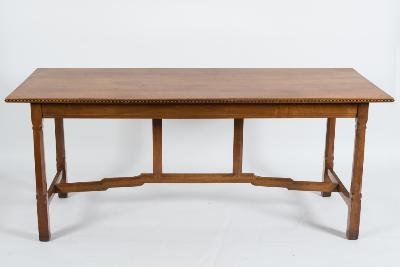 By Peter Waals (1870-1937) - Cotswold School - A walnut rectangular dining table, the top with a moulded and chequer strung edge, having a moulded frieze on octagonal gouged and knopped legs, united by a shaped stretcher with chamfered uprights, on square section feet, the top 183cm (6ft) x 76cm (2ft 6in). * Note - A dining table by Peter Waals was sold in these rooms July 2012 Lot 793A for £14, 500.