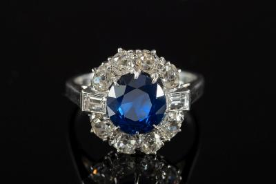 Sale FS25; Lot: 0242: A sapphire and diamond circular cluster ring with central round sapphire approximately 7.9mm diameter, claw-set within a surround of old brilliant-cut diamonds and between baguette-cut diamond shoulders, the diamonds estimated to weigh a total of 1 0cts, ring size 'N'.