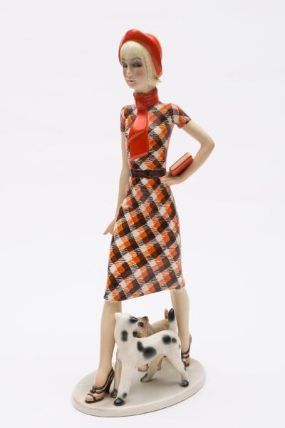A Lenci earthenware figure 'Zizi' after an original by Helen K?nig Scavini modelled as an elegant girl in red cap and checked dress carrying a book, two dogs at her feet, on oval base, painted marks 'Lenci Made in Italy, Torino - 77 XIII', circa 1934, 38.5cm high, [glue repair to book].