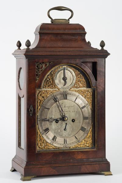 Thos. Langford, London, an 18th century mahogany bracket clock the eight-day duration, five-pillar double-fusee movement, now with an anchor escapement, having c-scroll and floral engraving to the backplate and striking the hours on a bell, the eight-inch break-arch brass dial having a raised silvered chapter ring engraved with black Roman numerals and outer five-minute outer Arabic markings, the centre with a subsidiary date dial and engraved with the maker's name Thos. Langford, London, the arch with a silvered strike/silent dial and all with gilt-metal cast c-scroll and floral spandrels, with blued steel hands, the bell-top mahogany case with inset brass fretwork to the top corners, brass acorn finials to the top, a brass carrying handle, glazed side panels and standing on brass bracket feet, height 51cm, not including handle.