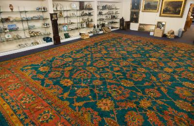 Sale FS25; Lot: 0751: A Turkish carpet of very large size, the blue/green field with an all over geometric design of interlaced serated palmettes and lanceolate leaves in principal colours of brick red, green and orange, enclosed by a main brick red palmette and foliate meander border, 812cm (26ft 8in) x 714cm (23ft 5in).