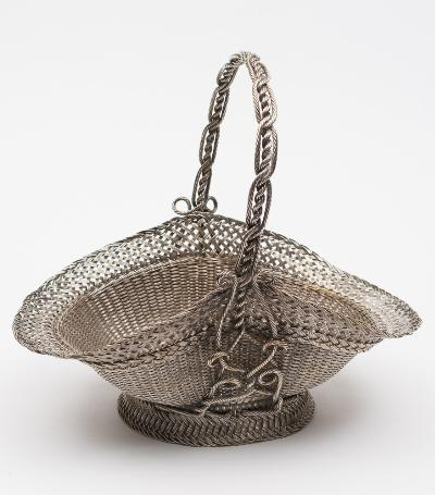 A silver plated fruit basket of woven wire work design with loop carrying handle, raised on a circular spreading foot, 29cm high.