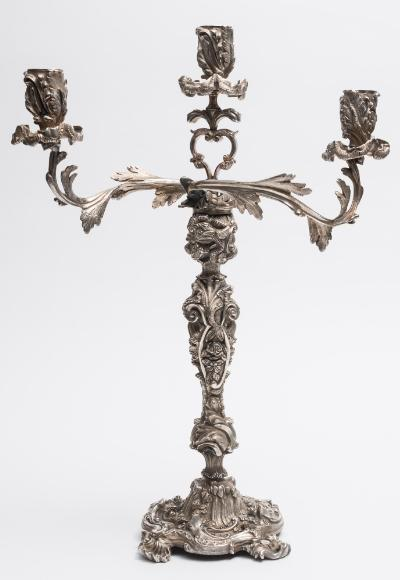 A plated twin-branch candelabra with foliate decorated nozzles on scrolling foliate branches issuing from a scroll and flowerhead decorated stem, on a square foliate and scroll base, 56cm high.