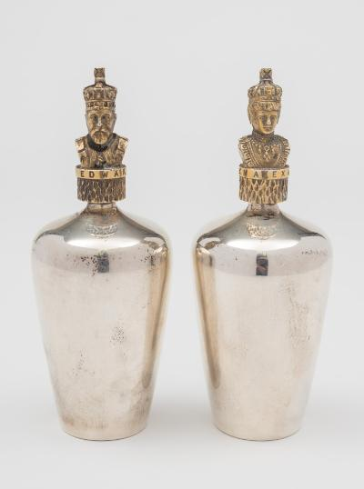 A pair of Elizabeth II silver commemorative perfume bottles by Stuart Devlin, London, 1977 the bottles of cylindrical tapering form, the stoppers modelled as portrait heads of King Edward VII and Queen Alexandra, contained in a fitted case with Ltd. Ed certificate No 8 of 25 retailed by Stanley Hall, London.