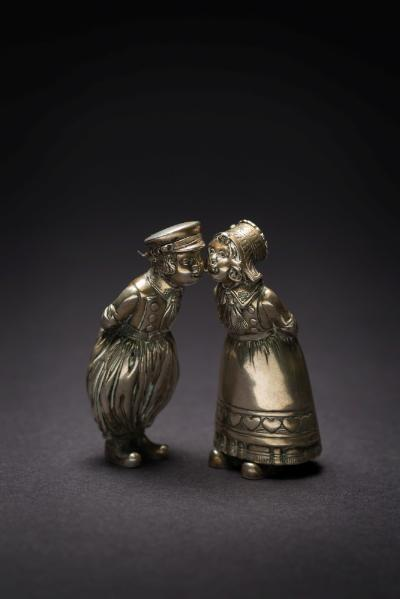 A pair of Continental silver novelty condiments in the form of a kissing couple in traditional Dutch costumes, their cap and bonnet having hinged lids, each 9.5cm high, 5.77ozs.