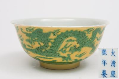 Sale FS26; Lot: 0456: A Chinese porcelain green enamelled yellow ground 'dragon' bowl the exterior incised and painted with a pair of dragons in pursuit of flaming pearls amongst clouds and lightning, six character Kangxi mark in concentric circles, 15cm diameter, [rim chip and cracks].