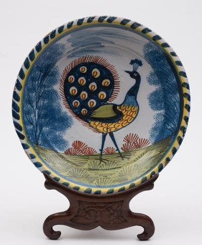A rare English delftware blue-dash charger painted in blue, yellow, iron-red and green with a large peacock displaying between trees with sponged leaves, within yellow line and blue-dash rim, the reverse tin glazed, probably Lambeth, circa 1720-40, 32cm diameter [minor damage, slightly misshapen].