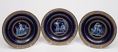Three Meissen porcelain plates each of circular form with pierced rim, the centre decorated in white enamel on a cobalt blue ground with classical Greek figures within gold borders, blue crossed swords with pommels, circa 1880, 23cm diameter.