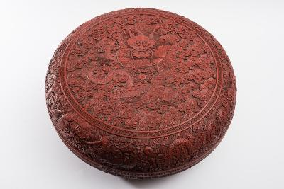 A fine and large Chinese red cinnabar lacquer 'Dragon' box and cover of circular form, the domed cover carved with a five-clawed dragon writhing around a flaming pearl surrounded by cloud scrolls, the sides with four further dragons and two pearls between key pattern borders, the base similarly carved, Qianlong/Jiaqing, 44cm diameter [some damage and wear].