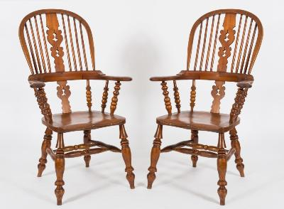 A pair of Victorian elm, ash and fruitwood stick back Windsor elbow chairs, the hoop backs each with a pierced central splat, having shaped solid seats on turned and tapered splayed legs, united by H stretchers.
