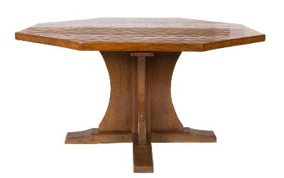 By Robert Thompson of Kilburn (The Mousman) - An oak octagonal dining table, the adzed top with concave edges, on curved cruciform pillar and trestle base, 135cm ()4ft 5 1/4in) across), 73cm (2ft 4 3/4in) high.