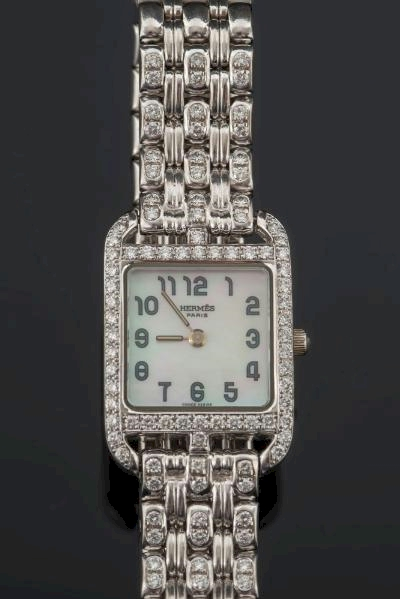 Sale FS27; Lot: 0166: Hermes. A lady's 18ct white gold and diamond mounted 'Cape Cod' wristwatch, the square mother of pearl dial with Arabic numerals surrounded by brilliant-cut diamonds in a case numbered 'CC1-192' and '1116434'.