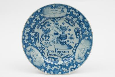 An English dated delftware plate painted in blue with a Chinese vase of flowers and a flower table by a trellis fence and inscribed 'Ann Pearson Born 17th May 1732', within a blue ground floral and scrollwork border reserved with three panels depicting Chinese river landscapes, probably London, 23cm diameter. *See: Louis Lipski and Michael Archer 'Dated English Delftware' page 86 plate 362 for a plate from the same series dated 1730.