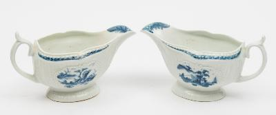 A pair of Worcester First Period porcelain sauceboats of press moulded form with panelled fluted exteriors painted in blue in the Little Fisherman pattern below a foliate and diaper border pattern, the interior with a floral spray, open crescent marks, circa 1765, 16cm long, [some bleed on one border].