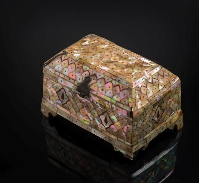 Sale FS27; Lot: 0612: A rare Indian mother of pearl and stone casket of rectangular form, the brass frame applied with polished red stone and mother of pearl plaques of fish-scale and foliate design secured with metal pins, with iron hinges and clasp, on shaped bracket feet, Gujarat, 17th century, 20cm wide [some old damage and losses].