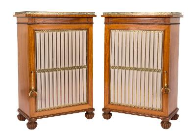A pair of 19th Century satinwood dwarf side cabinets in the Regency taste, with pierced brass galleries and beaded friezes, fitted with adjustable shelves enclosed by a pair of brass grille and pleated beige silk panel doors, on reeded bun feet, 66.5cm (2ft 2 1/4in) wide, 101cm (3ft 3 3/4in) high.
