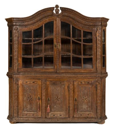 An 18th Century Flemish carved oak display cabinet, of large size, the domed upper part with a moulded dentil broken pediment and inscription to the tassel hung frieze, enclosed by a pair of glazed panel doors flanked by stiles with flowerheads and continuous scrolls and glazed panel canted sides, the lower part with a dentil edge, enclosed by three panel doors, decorated with entwined tassels, flowerheads and inlaid stellar ornament between similar stiles and canted angles on bun shaped feet, 225cm (7ft 4 1/2in) wide, 244cm (8ft) high.