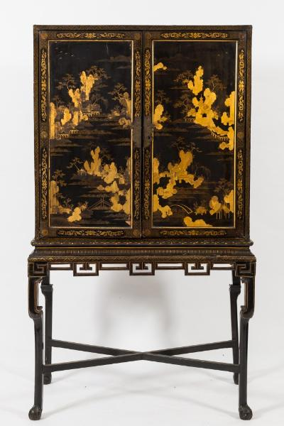 Sale FS28; Lot: 0941: An early 19th Century Chinese black lacquer and gilt heightened cabinet on stand, the architectural interior fitted with small drawers and shelves with giltwood uprights and pierced fretwork aprons and galleries, decorated with bamboo and prunus trees and pagodas in garden landscapes, having a central scroll flanked by inscription panels and hanging lanterns, enclosed by a pair of doors further decorated with pagoda garden landscapes, the sides with applied brass carrying handles, the later stand with a pierced fret geometric apron on shaped legs, united by X-frame stretcher, terminating in claw and ball feet, the cabinet 99cm (3ft 3in) wide, 181.5cm (5ft 11 1/2in) overall height.