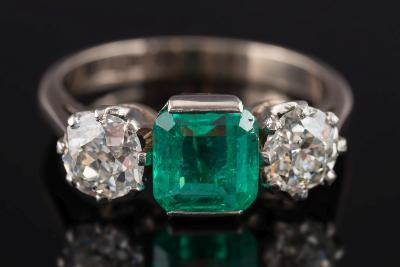 An 18ct white gold, emerald and diamond three stone ring, the central emerald-cut emerald approximately 6mm long x 6mm wide between circular, old brilliant-cut diamonds each approximately 0.60ct, in rex claw setting, ring size Q.