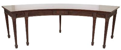A George III mahogany sideboard table, of arc outline with a plain top, the fluted frieze with a central panel decorated with ribbon tied pendant husks centred by a paterae roundel, on square fluted tapered legs terminating in spade feet, 10ft 4in (315cm) across, maximum, 3ft (91.5cm) high.