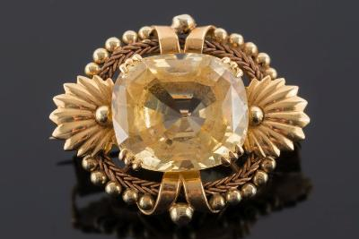 Sale FS29; Lot: 0241: A mid 20th century gold and yellow sapphire single-stone brooch, the cushion-shaped yellow sapphire approximately 18.3mm long x 16mm wide x 10.3mm deep, within a beaded and shell motif frame.