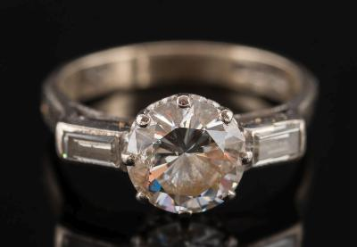 An 18ct white gold and diamond single stone ring, the circular, brilliant-cut diamond estimated to weigh 2.2cts, between baguette-cut diamond, single stone shoulders, ring size M.