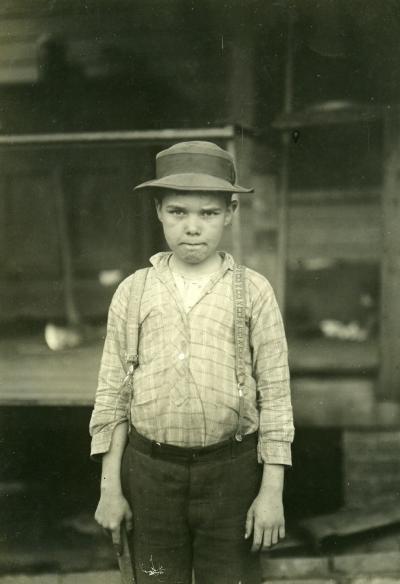 Lewis Wickes Hine [1874-1940, Winsconsin, USA] - George, a worker in a Cotton Mill vintage gelatin-silver print - image 11.5 x 8.5cm, sheet size 17 x 12cm Inscribed and initialled by Hine on the reverse of the print 'George, a worker in a cotton Mill. Mother said he had just reached 11 years and has been working on and off for over a year. He makes 5.50 dollars a week. father works in Mill, April 1913. F W.H'.